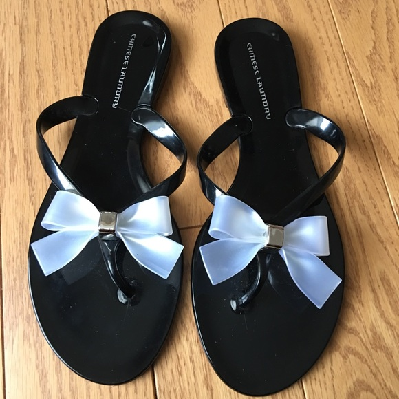 6c45e0f3241fea Chinese Laundry Shoes - Black flip flops with a white plastic bow size 7